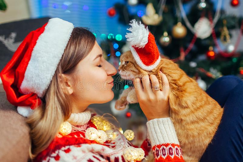 Christmas celebration with cat. Woman playing and kissing pet in Santa`s hat by New year tree at home royalty free stock photography