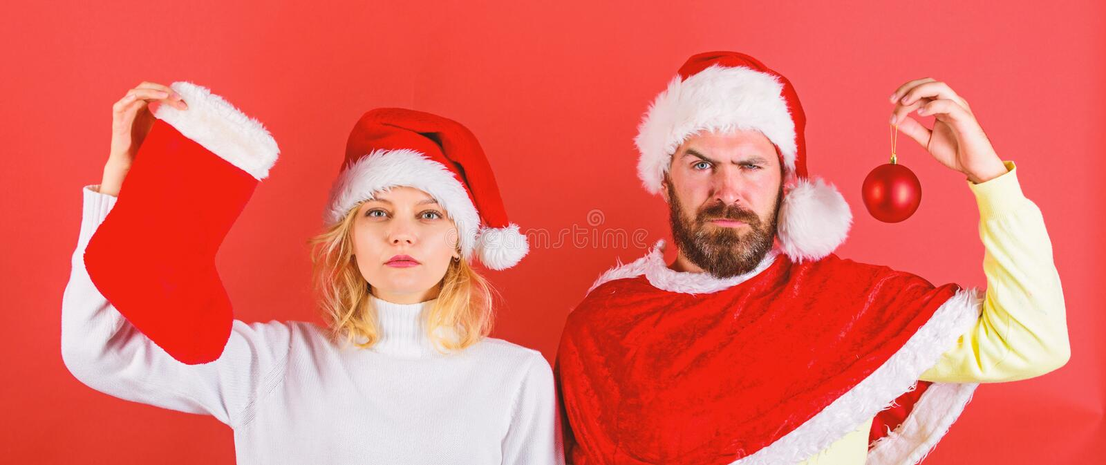 Christmas celebration concept. Woman and bearded man in santa hat waiting christmas red background. Christmas stocking stock images