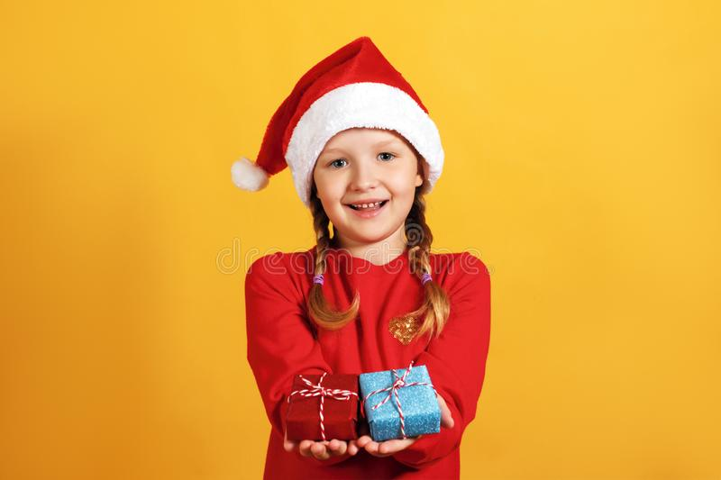 Christmas celebration. Happy little girl in santa hat holds small boxes with gifts in hands on a yellow background royalty free stock image