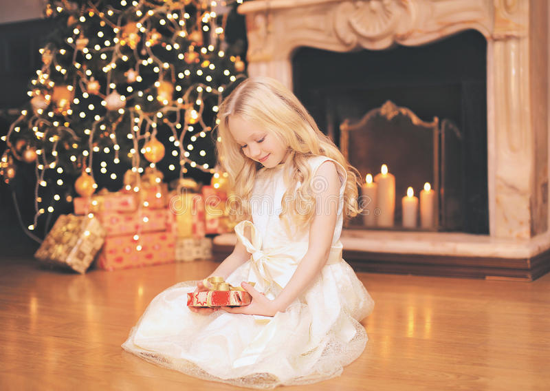 Christmas, celebration, holiday, xmas concept - happy little girl with gifts near christmas tree and fireplace stock photo