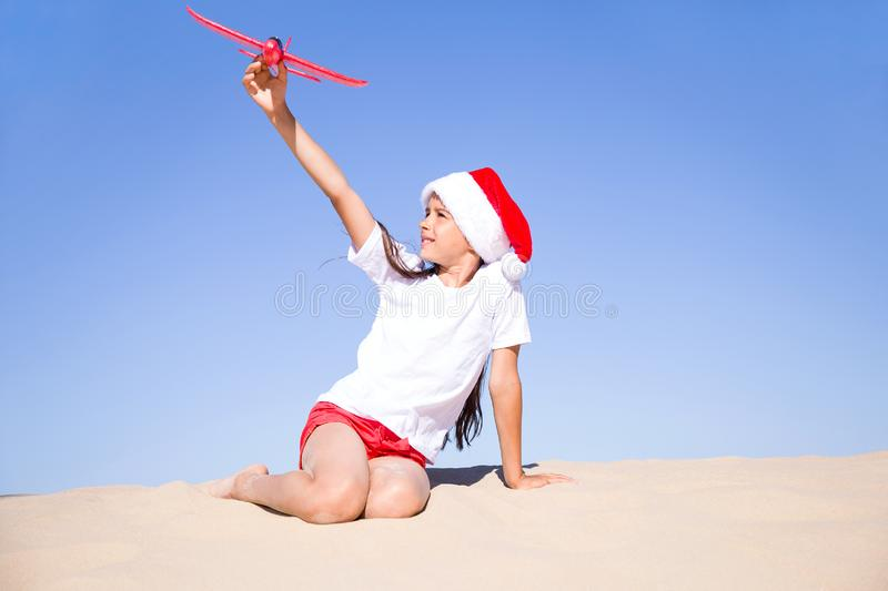 Happy cute little girl wearing a red Santa hat sitting on the sandy beach by the sea and playing with the red toy plane. Christmas celebration vacations on a royalty free stock images