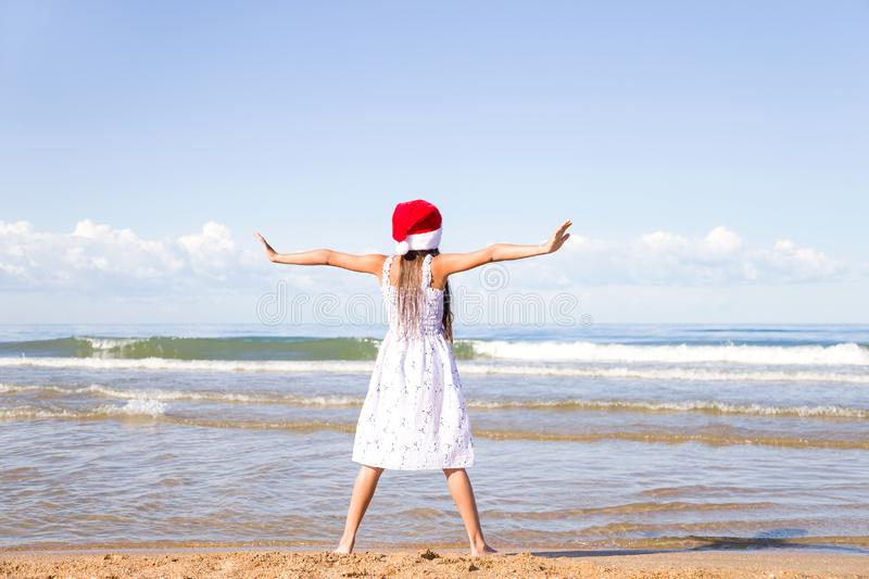 Happy little girl wearing a red Santa hat standing arms outstretched on the sandy beach by the sea on clear sunny day royalty free stock image
