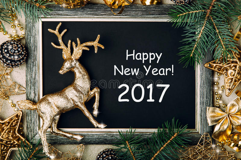 Christmas chalk board with golden frame. Golden deer figure with Christmas decorations and fir branches on black background, New Year frame, top view, copy space stock images