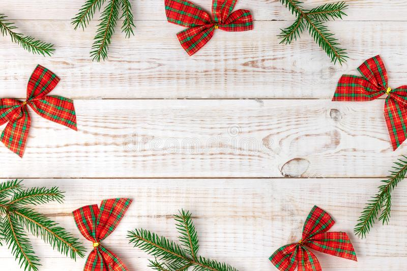 Christmas checkered bows with green fir tree branches making a border or frame for your text, creative minimalistic composition on royalty free stock photos
