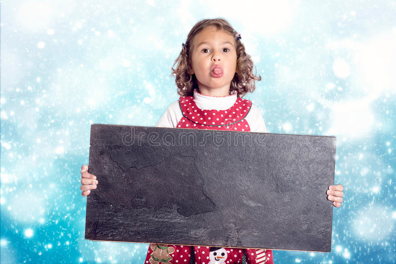 Christmas child with chalkboard. Little child holding blank chalkboard,Christmas concept stock image
