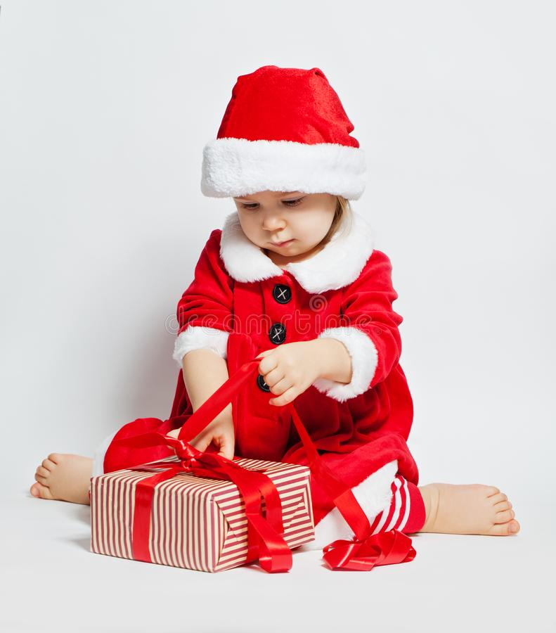 Christmas child girl in Santa hat opening Xmas gift box stock photo