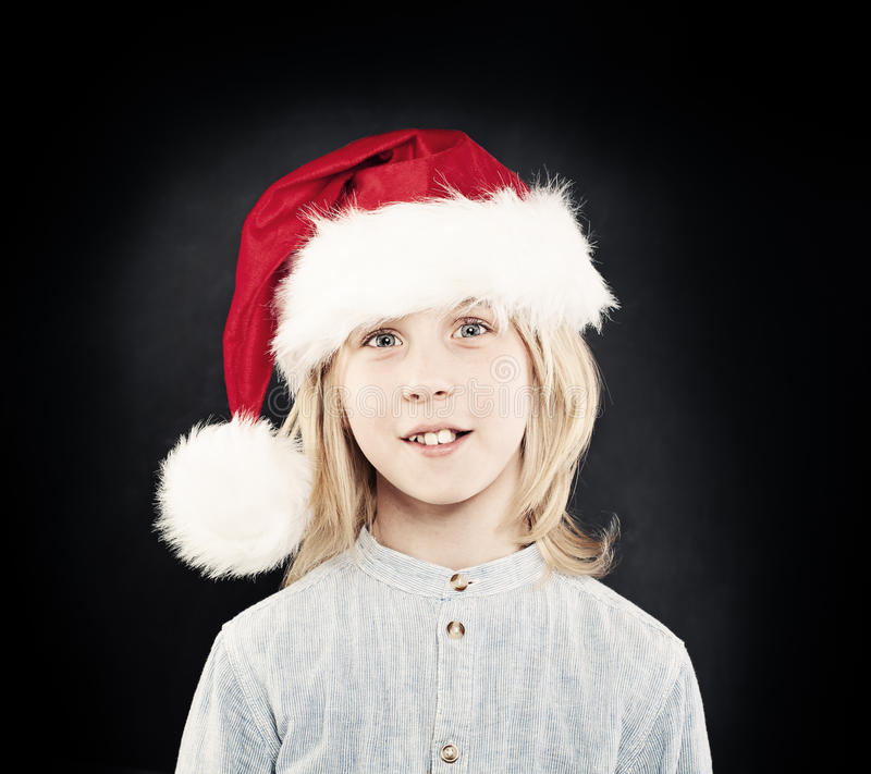 Christmas Child. Happy Little Boy in Red Santa Hat. Studio Portrait royalty free stock photos