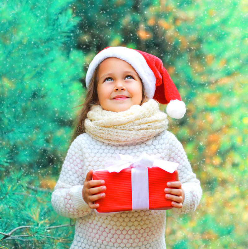Christmas child little girl in santa red hat with gift box dreaming near tree stock photo