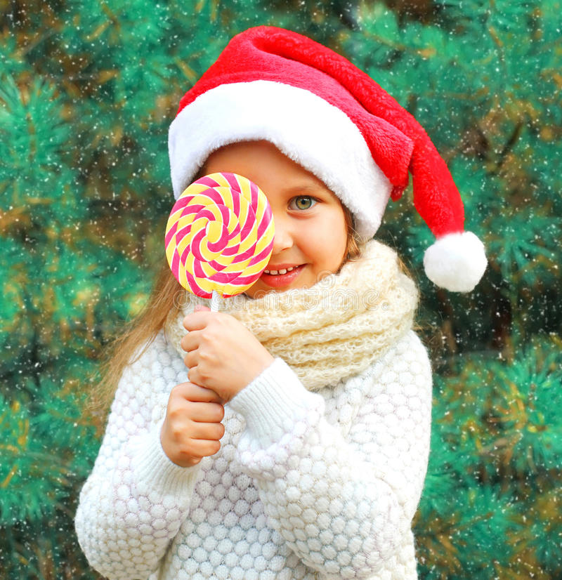 Christmas child little girl in santa red hat with sweet lollipop near tree stock image
