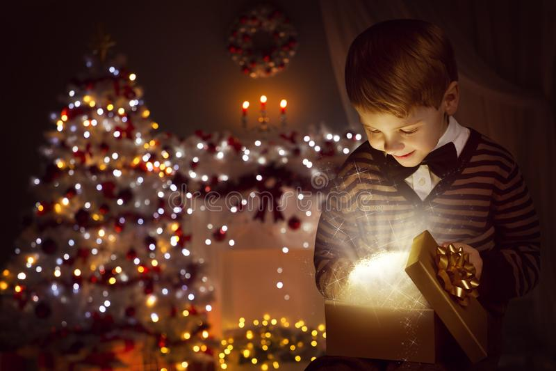 Christmas Child Open Present Gift Box, Happy Kid Opening Giftbox in Xmas Tree Home Interior stock image