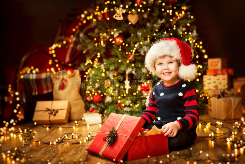 Christmas Child Open Present under Xmas Tree, Happy Baby Boy royalty free stock photo
