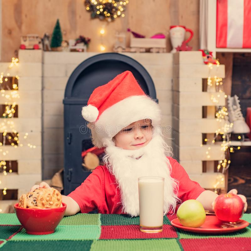Christmas child. Thanksgiving day and Christmas. Santa Claus. Santa boy child eating cookies and drinking milk. stock photo
