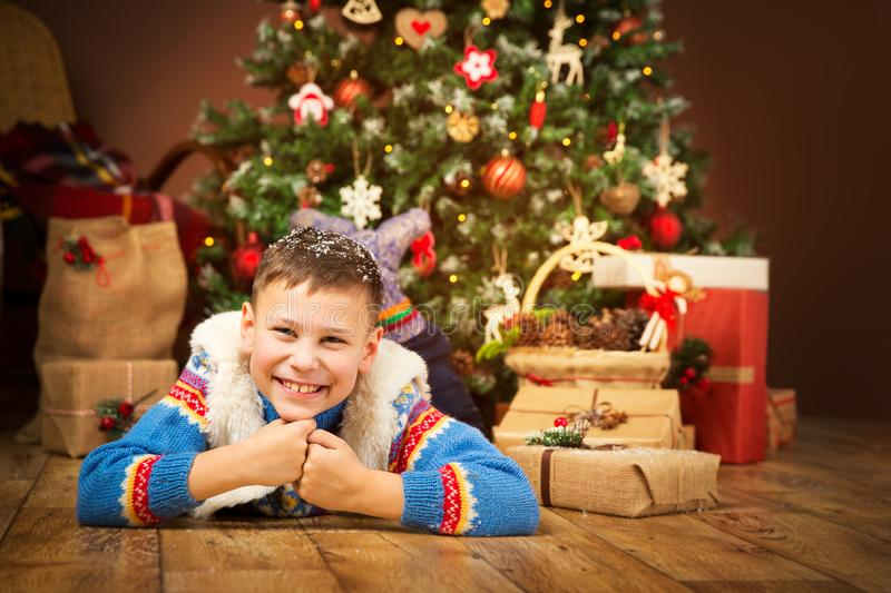 Christmas Child under Xmas Tree, Happy Boy Presents Gifts. Christmas Child under Xmas Tree, Happy Boy Kid lying on wood floor front of New Year Presents Gifts stock photo