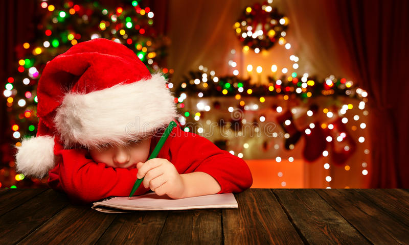 Christmas Child Write Letter Santa Claus, Kid in Hat Writing. Christmas Child Write Letter to Santa Claus, Kid in Santa Hat Writing Wish List, unfocused lights royalty free stock images