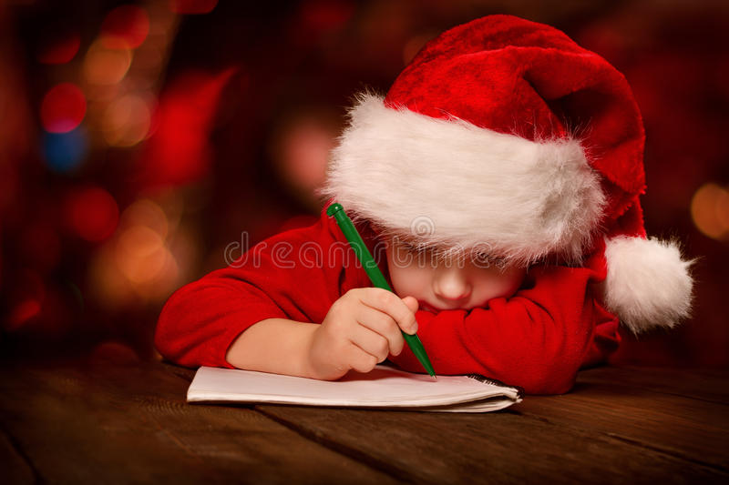 Download Christmas Child Writing Letter In Red Santa Hat Stock Image