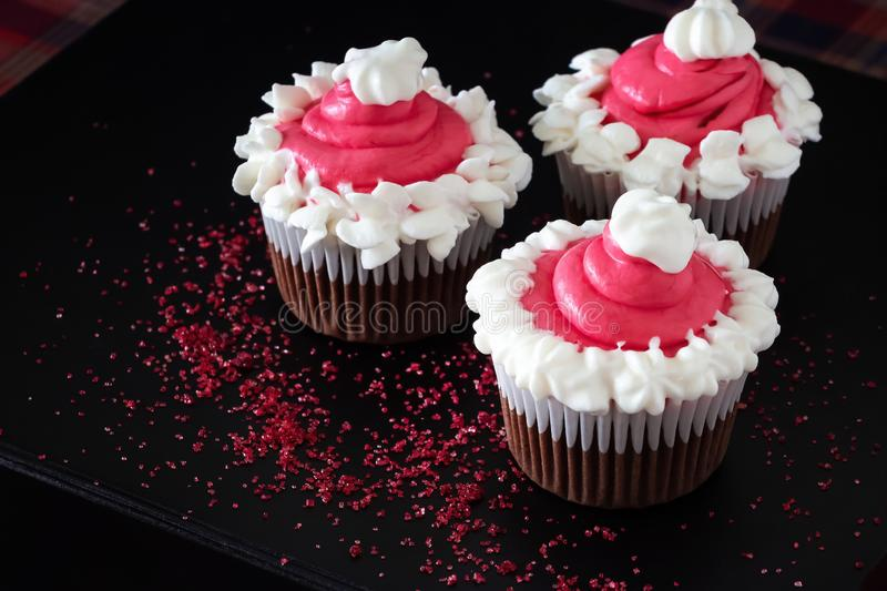 Christmas chocolate cupcakes pink cream cheese frosting. Dark background. Selective focus royalty free stock photo