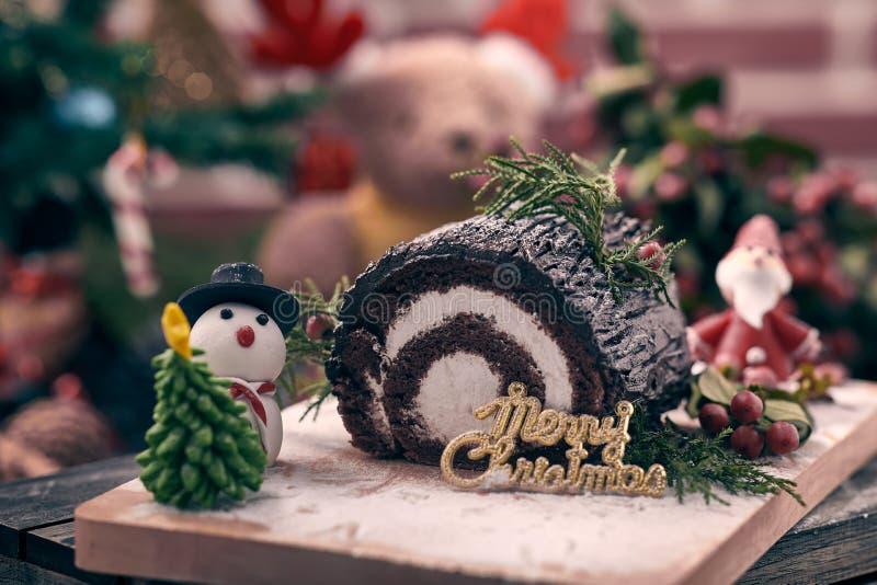 Christmas chocolate roll cake placing together with snow man, Santa Claus sugar, Christmas tree and blue burry. Christmas chocolate roll cake placing together stock photo