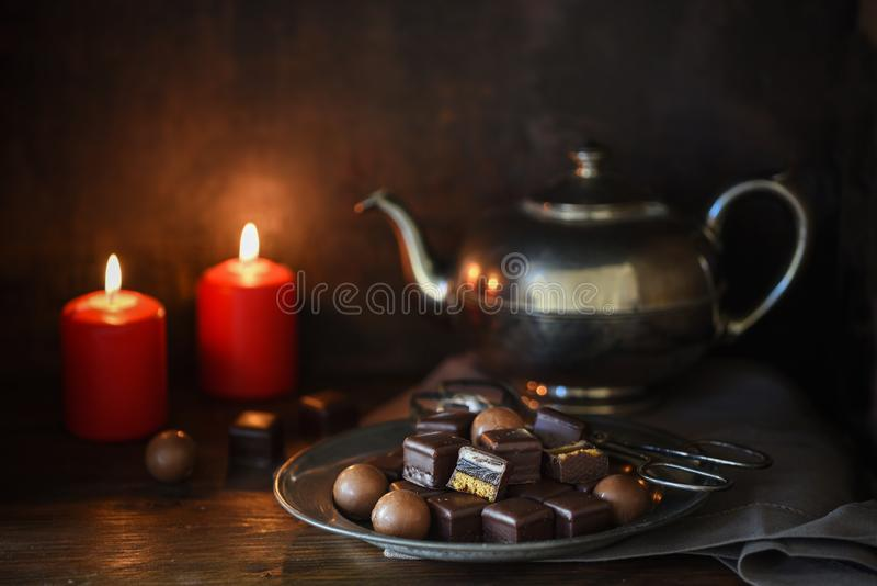 christmas chocolate sweets, two red candles and a silver teapott on a rustic wooden table, dark moody background royalty free stock photos
