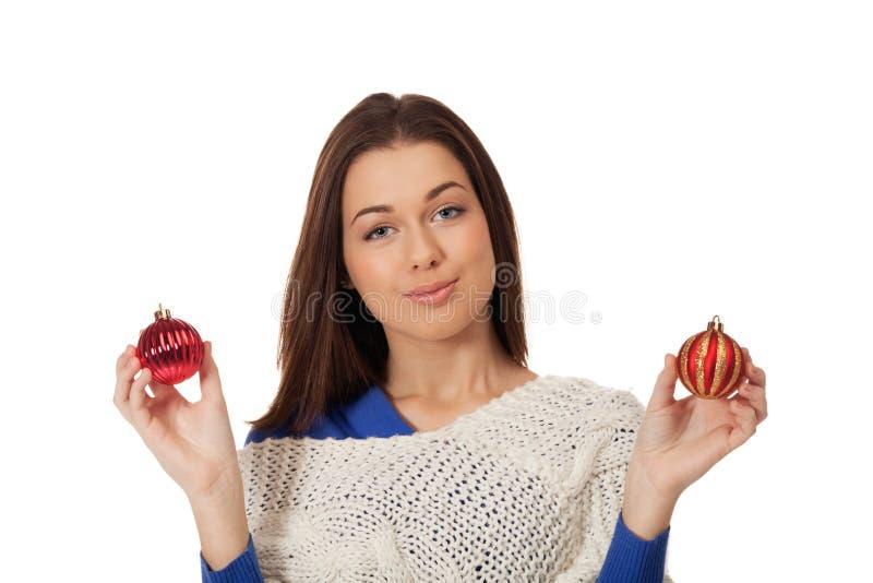 Christmas choice. Young girl having hard times chosing Christmas decoration royalty free stock photography