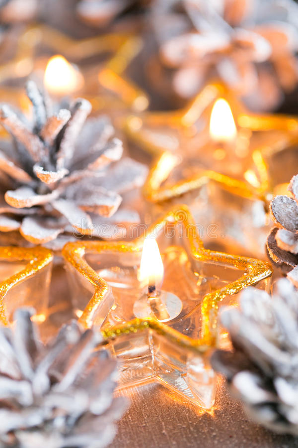 Christmas. Christmas card with glowing small candle and fir cone. Christmas card with glowing small candle and fir cones on old wooden background stock image