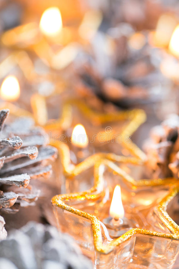 Christmas. Christmas card with glowing small candle and fir cone. Christmas card with glowing small candle and fir cones on old wooden background royalty free stock photos