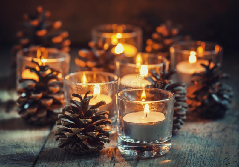 Christmas Christmas card with glowing small candle and fir cones. On old wooden background, dark toned image in country style, selective focus stock photo