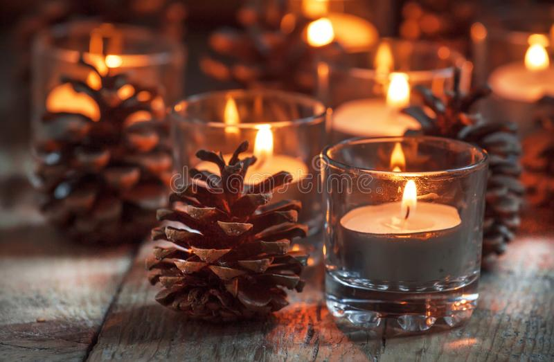 Christmas Christmas card with glowing small candle and fir cones. On old wooden background, dark toned image in country style, selective focus royalty free stock images