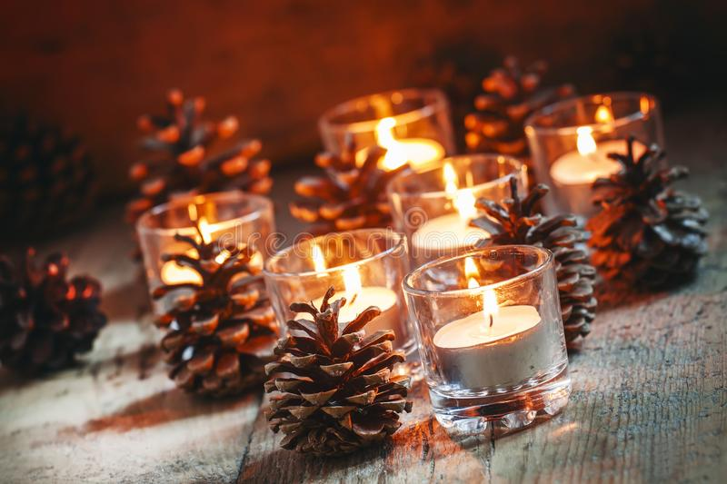 Christmas Christmas card with glowing small candle and fir cones. On old wooden background, dark toned image in country style, selective focus royalty free stock image