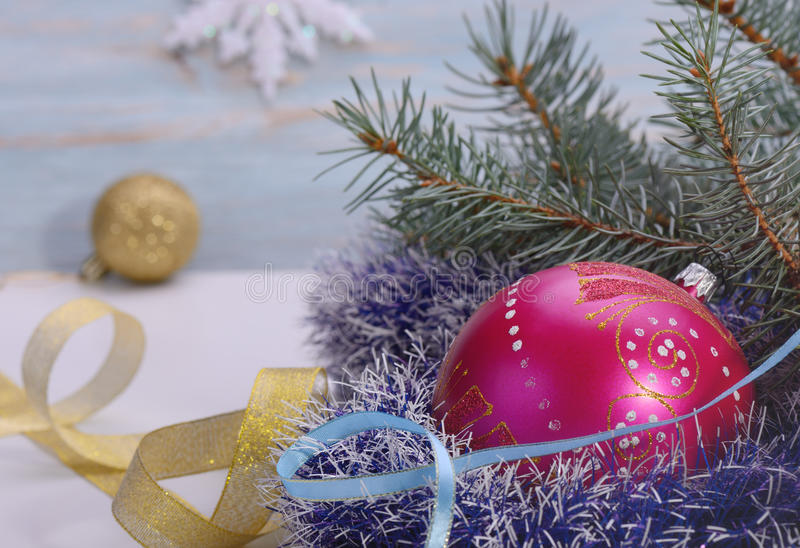 Christmas .Christmas toys. Red ball surrounded by fir tree branches, and a Golden ribbon light blue background blur snowflake stock photos