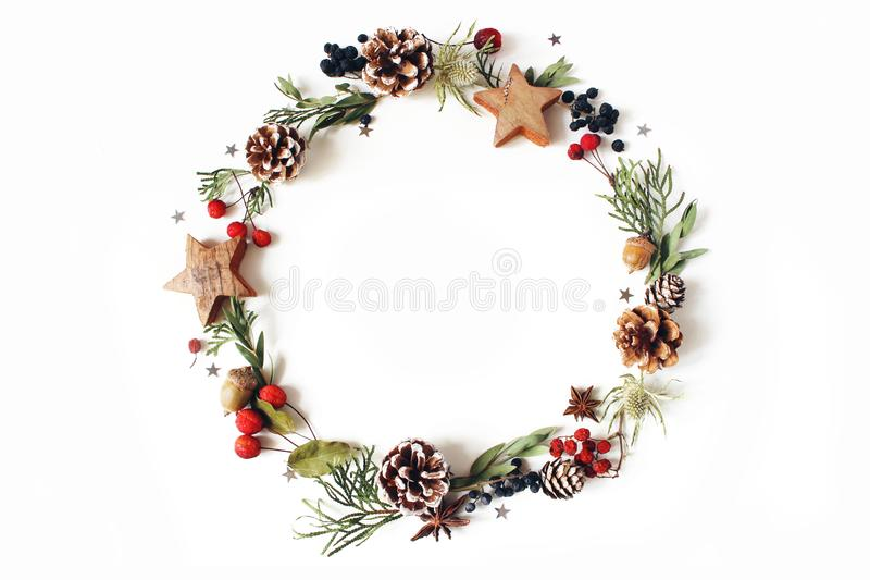 Christmas circle floral composition. Wreath of cypress, eucalyptus branches, pine cones, rowan berries, anise, confetti. Stars and sea holly flowers on white royalty free stock photos