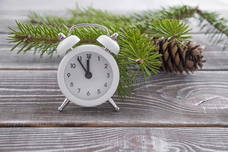 Christmas clock on the desk. A branch of a tree and a lump. New Year. Time concept stock photos