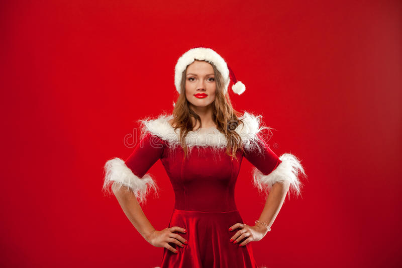 Christmas Close up portrait of beautiful girl wearing santa claus clothes, over red background stock image