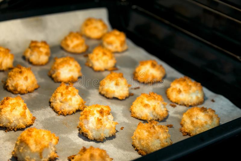 Christmas coconut puffs macaroon cookies on parchment paper on tray in oven. Festive cozy home atmosphere. Holiday pastry baking stock image