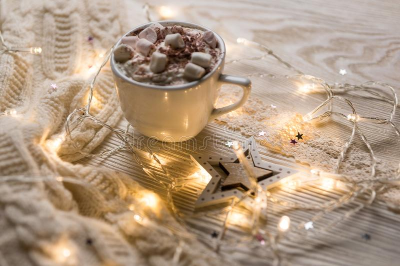Christmas coffee cup with marshmallows. Still life on white background. New Year`s lights and decorations stock images