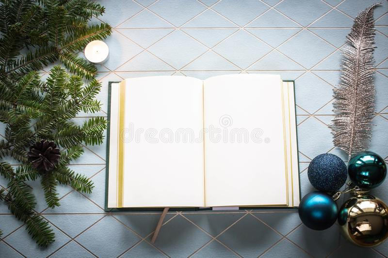 Christmas collage with notebook, Christmas tree branches, Christmas decorations on a modern, designer background in pastel blue. stock photos