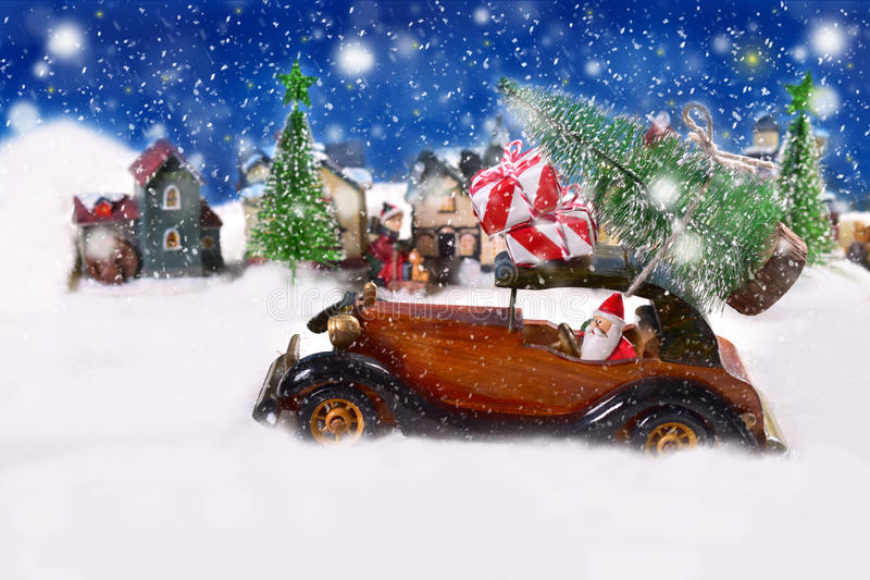 Christmas is coming. Christmas eve snowy night scene with santa claus driving old wooden car with gifts and christmas tree stock photo