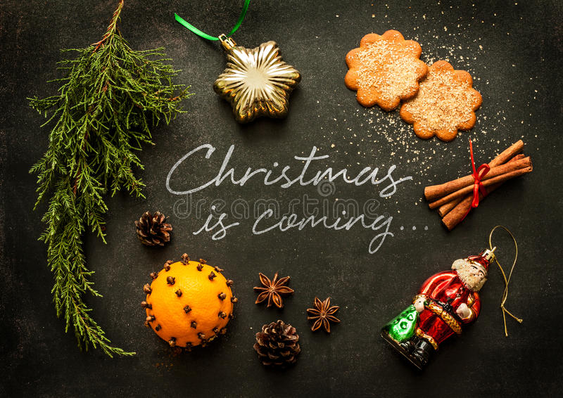 Christmas is coming - poster or postcard design. Vintage decorations, ginger cookies and spices on black chalkboard from above stock photo
