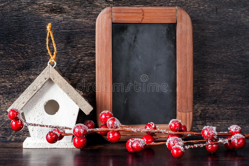Christmas composition: birdhouse, chalk board and a branch with berries royalty free stock images