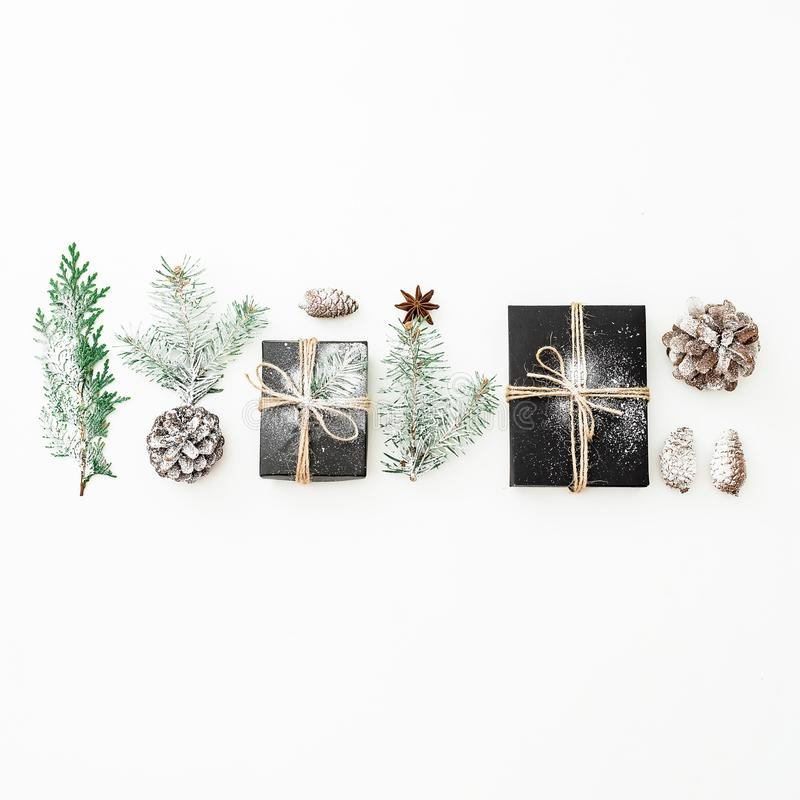 Christmas composition of black gift box with snow, fir branches and pine cones on white background. New year concept. Flat lay. To. Christmas composition of stock image