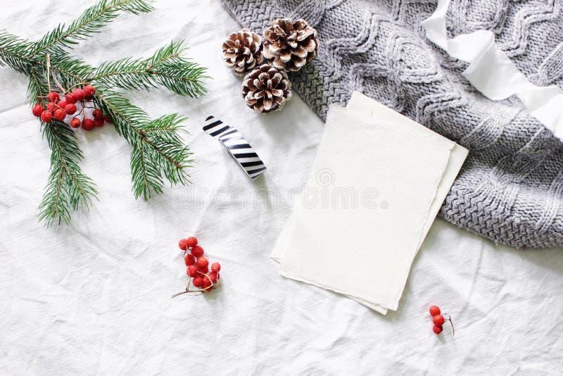 Christmas composition. Blank greeting card, wish list mock-up scene. Christmas tree branch, red rowan berries, pine stock photos