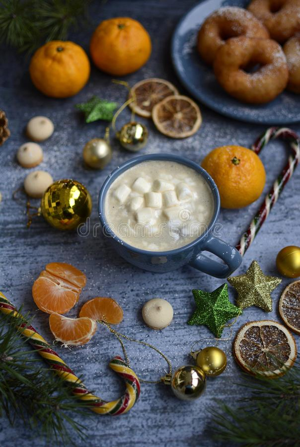 Christmas composition on a blue background from Christmas balls, candies, tangerines, coffee mugs and marshmallows, donuts and fir royalty free stock images
