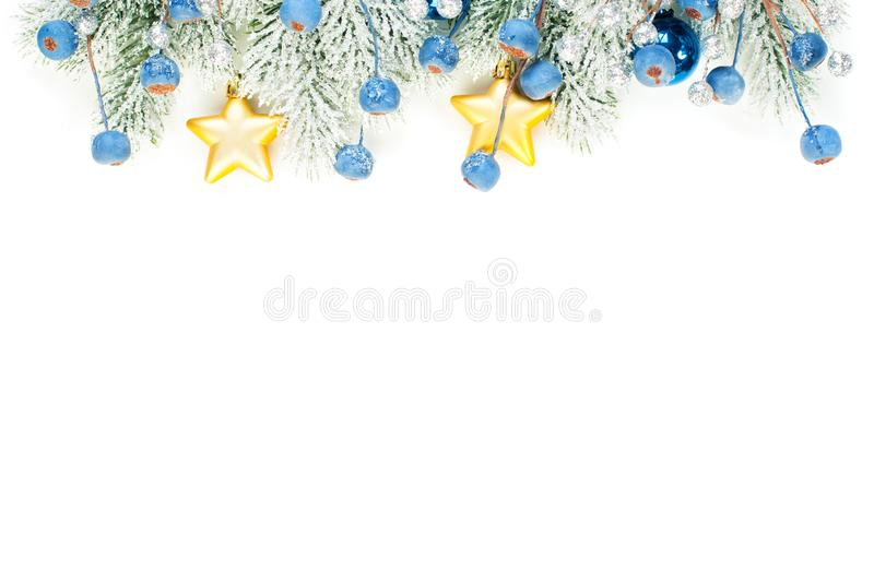 Christmas composition border with blue frozen berries, stars, gold garland and Xmas tree branch isolated on white background. Colorful Xmas decorations stock image
