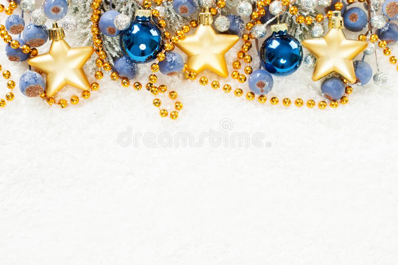 Christmas composition border with blue, gold and silver decor on white snow background.  royalty free stock image