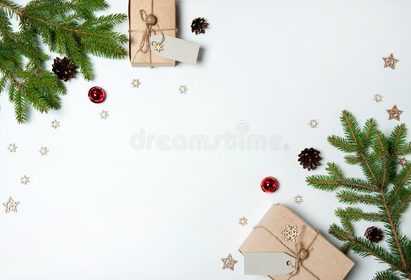 The border is made of gift boxes, fir branches, pine cones, red bells, wooden decorative snowflakes and stars on a white backgroun stock photo