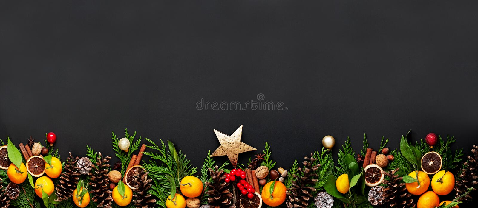Christmas composition with branch of Christmas tree, tangerines, Christmas ornaments, pine cones on a black background. stock photography