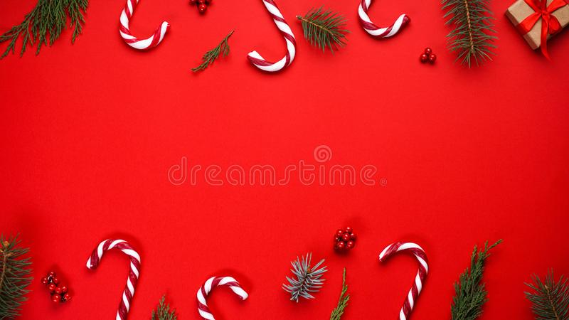 Christmas composition with candies and Christmas decoration on a red background, place for text. Flat lay stock photo