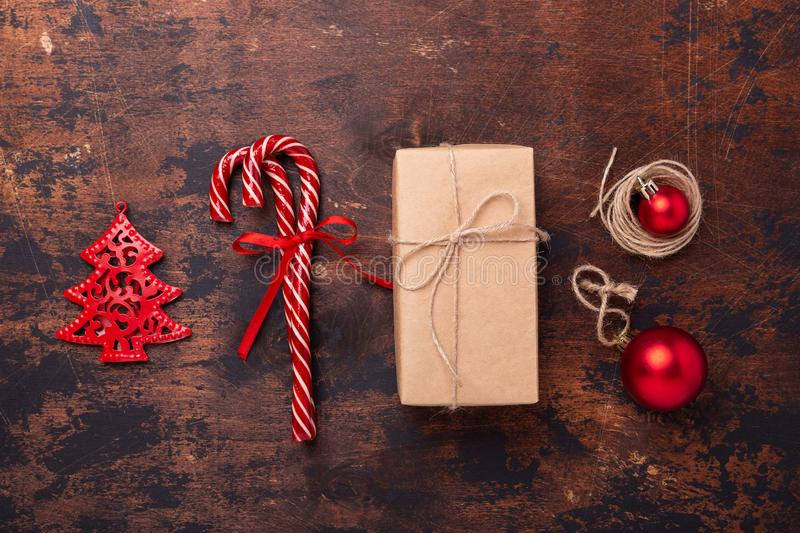 Christmas composition with candy canes, present box and gifts. Red and craft decoration on wooden background royalty free stock images