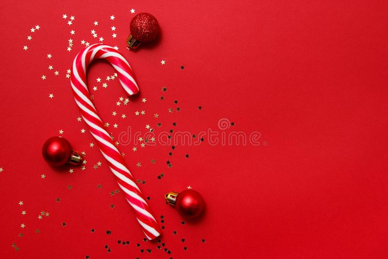 Christmas composition. Candy with star confetti and balls on red background. Winter, new year concept. Flat lay, top view, copy royalty free stock photography