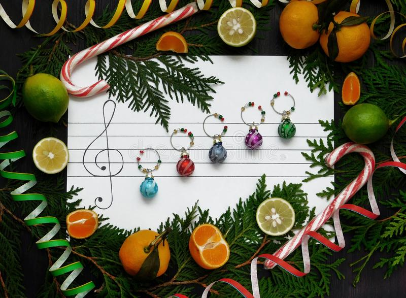 Christmas composition. Christmas decoration balls are arranged on the paper like music notes royalty free stock photo