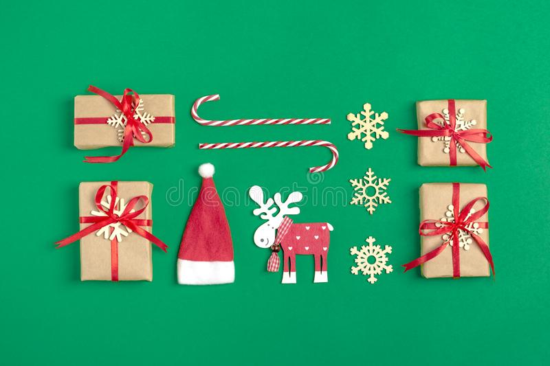 Christmas composition. Christmas decoration gifts, , Santa Claus hat , candy, snowflakes on green background. stock photos